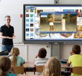 Zdjęcie przedstawia nauczyciela prowadzącego lekcje z użyciem monitora interaktywnego.